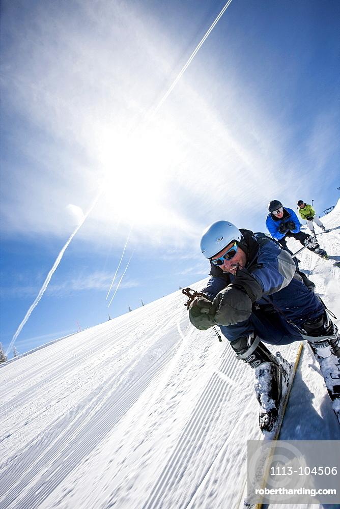 Three skiers on slope, Fageralm, Salzburg, Austria