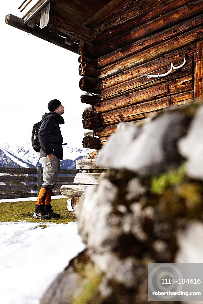 Hiker and wooden alpine hut, descent from Unnutz Mountain (2078 m), Rofan Mountains, Tyrol, Austria