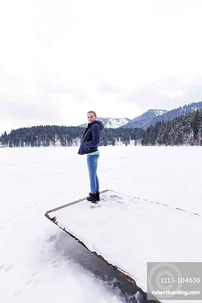 Young woman on a jetty at lake Spitzingsee, Upper Bavaria, Germany