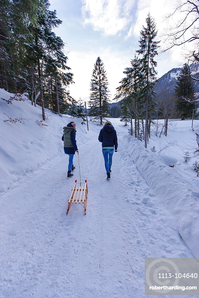Two young women with a sled, Spitzingsee, Upper Bavaria, Germany