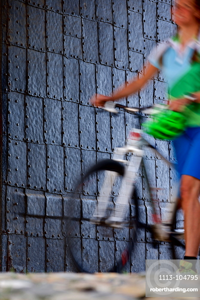 Woman pushing a bicycle, Burghausen, Chiemgau, Bavaria, Germany