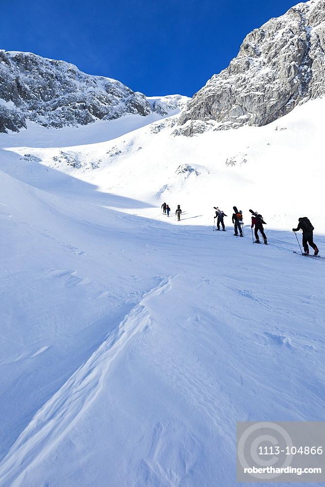 Backcountry skiers and snowboaders ascending Sonntagskogel peak, Tennengebirge mountains, Salzburg, Austria