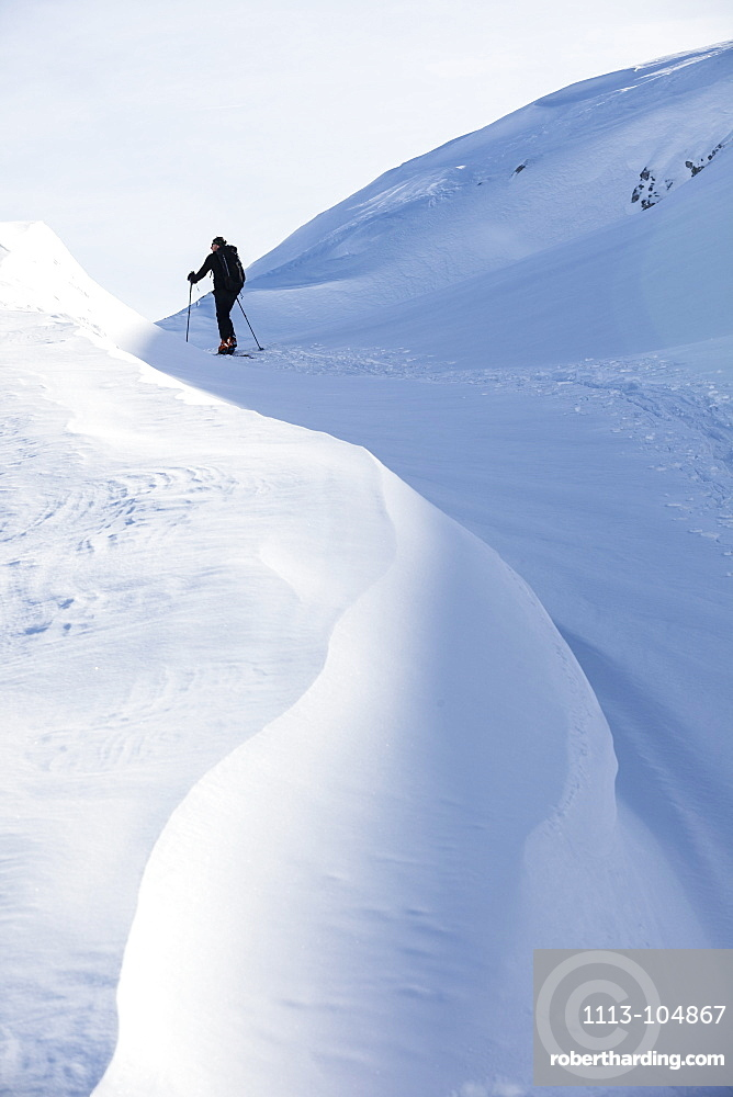 Backcountry skier ascending Sonntagskogel peak, Tennengebirge mountains, Salzburg, Austria