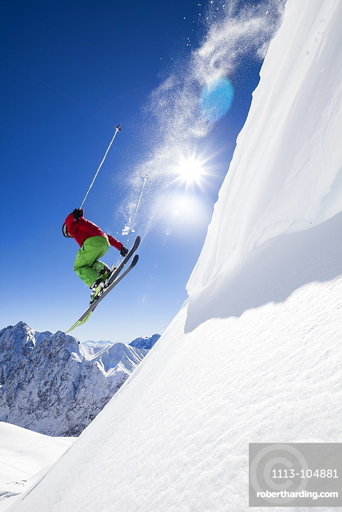 freeride skier jumping over snow cornice, Zugspitze, Hochwanner and Gatterl in the background, Upper Bavaria, Germany