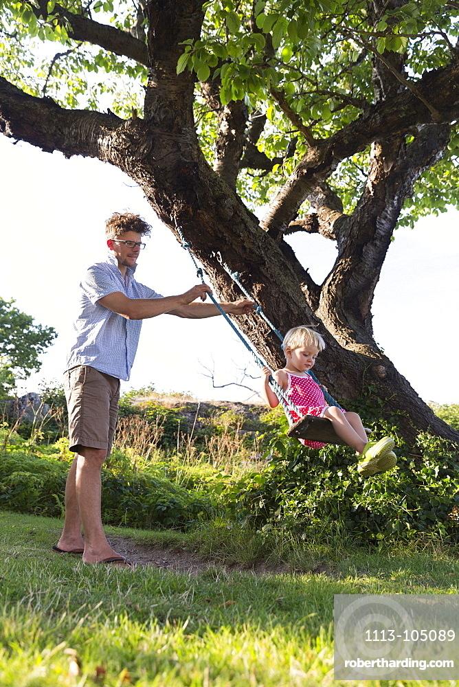 Father pushing young daughter on the swing, Summer, Baltic sea, MR, Bornholm, Svaneke, Denmark, Europe