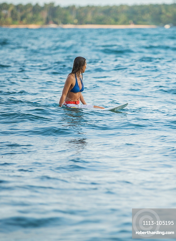Young female surfer waiting for a wave in the water, Sao Tome, Sao Tome and Principe, Africa