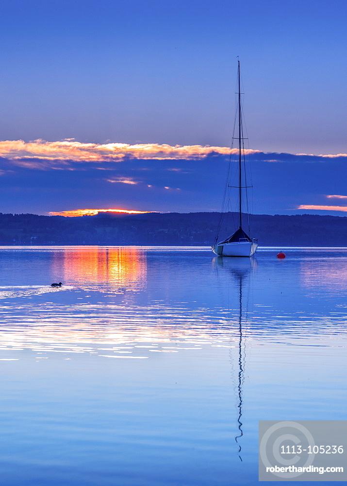Boat in backlight at sunrise on Lake Starnberg, Tutzing, Bavaria, Germany