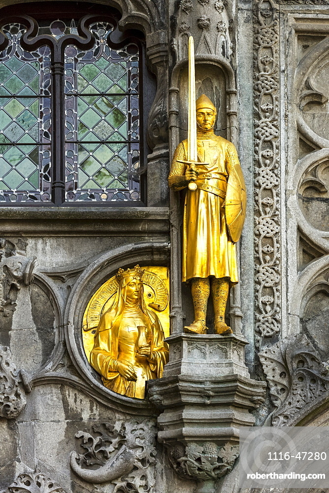 Close-up of a gold statue on a decorative building facade, Bruges, Belgium