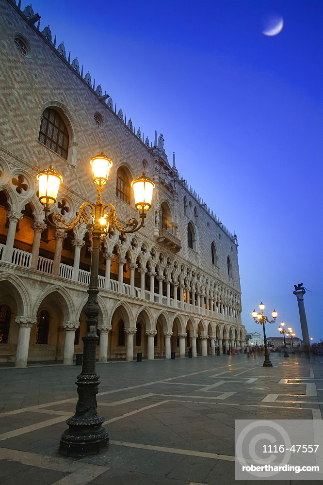 Doge's Palace at dusk with illuminated lamp posts and a moon in the blue sky, Venice, Italy