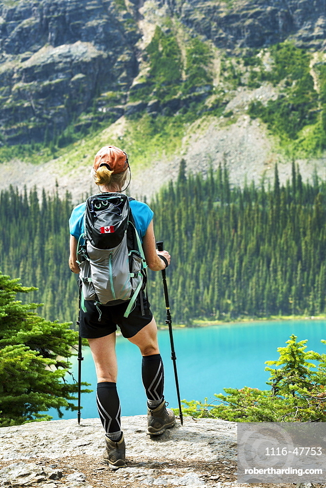 Female hiker standing on rocky cliff overlooking colourful alpine lake and mountain cliff in the background, British Columbia, Canada