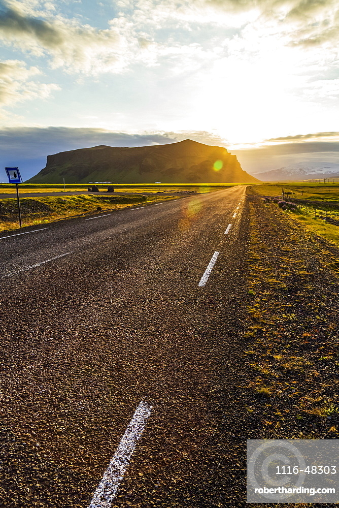 The sun sets behind the hills with a paved highway road leading into the sunset, Iceland
