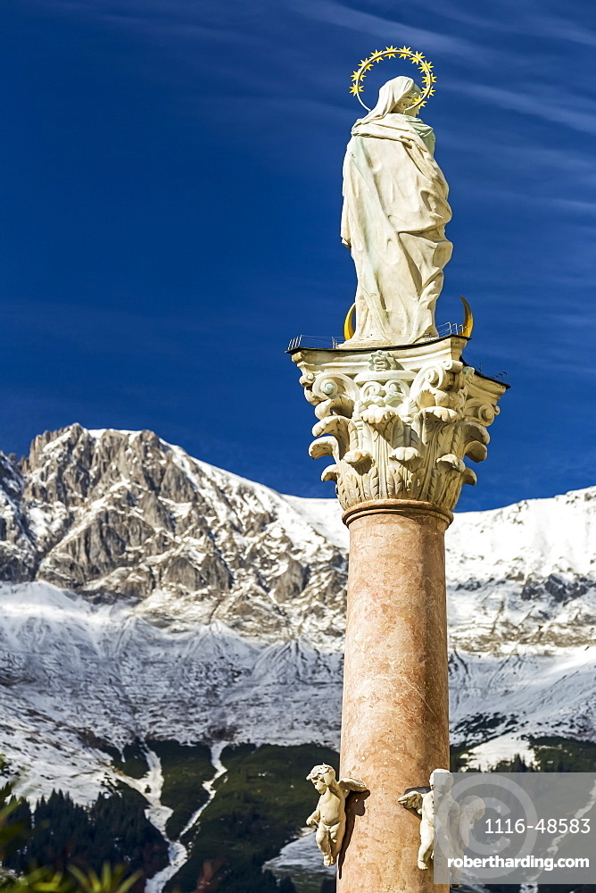Stone statue with halo on top of column with snow-covered mountain range and blue sky in the background, Innsbruck, Tyrol, Austria