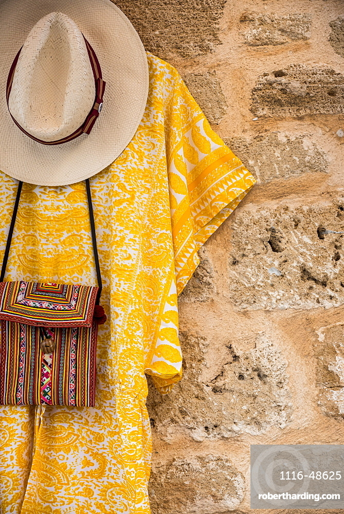 Clothes and accessories hanging on display against a stone wall, Alcudia, Mallorca, Balearic Islands, Spain