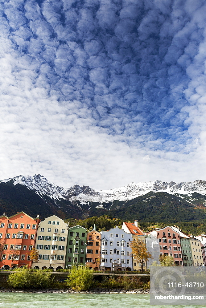 Colourful buildings along river bank with snow-covered mountain peaks, dramatic clouds and blue sky overhead, Innsbruck, Tyrol, Austria