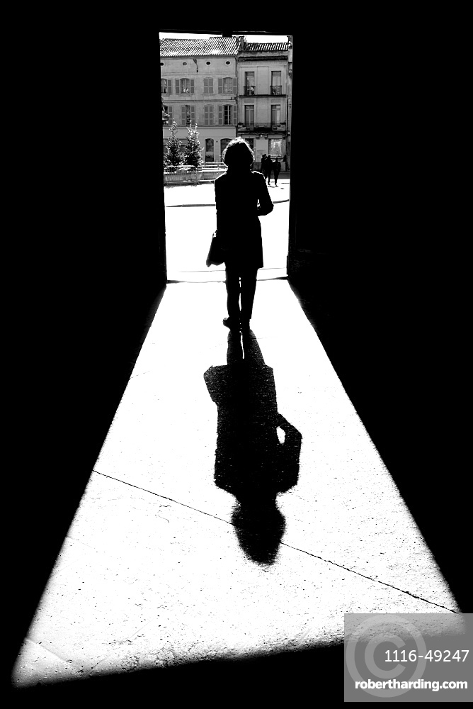 Silhouette and shadow of a woman going through a doorway to a town square towards City Hall, Arles, Provence Alpes Cote D'Azur, France