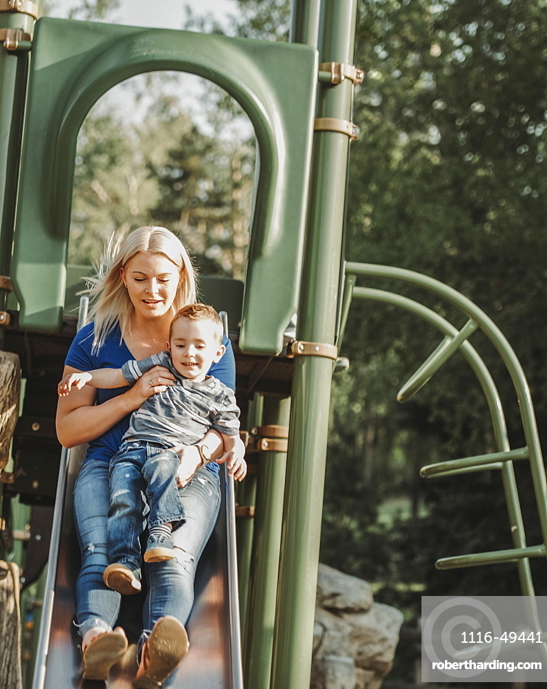 Mother on a slide with young son, Edmonton, Alberta, Canada