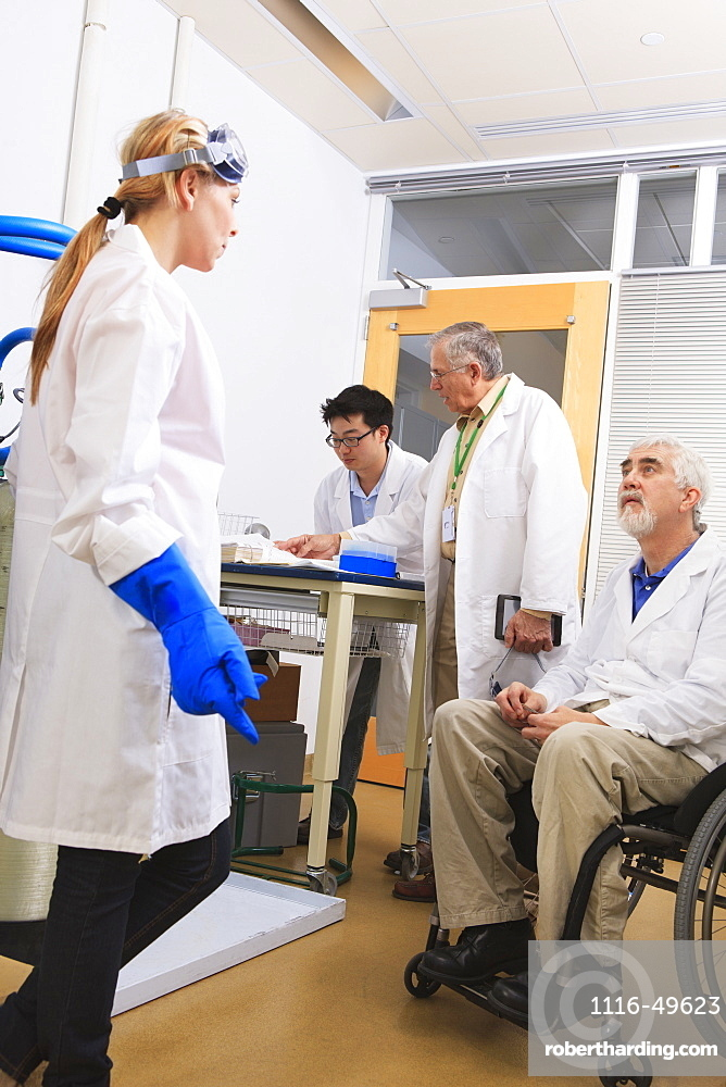 Professor with muscular dystrophy with engineering student and professor discussing log book for water distillation system in a laboratory