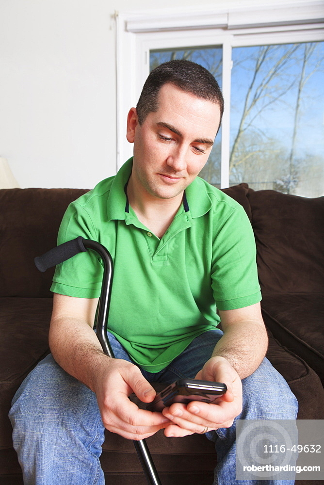 Man after anterior cruciate ligament (ACL) surgery with cane and a smartphone
