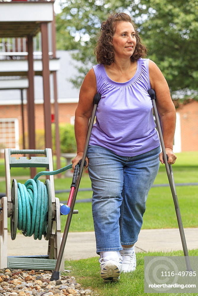 Woman with Spina Bifida walking with crutches and pulling garden hose