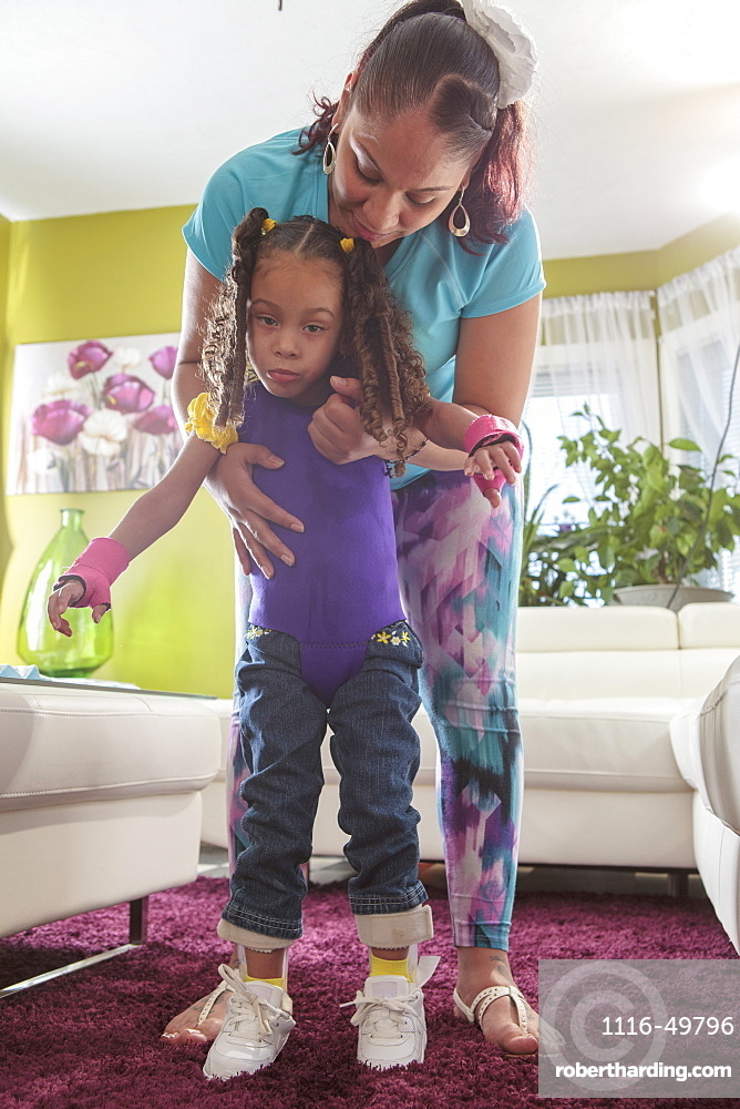 Mother helping small daughter walk with Cerebral Palsy