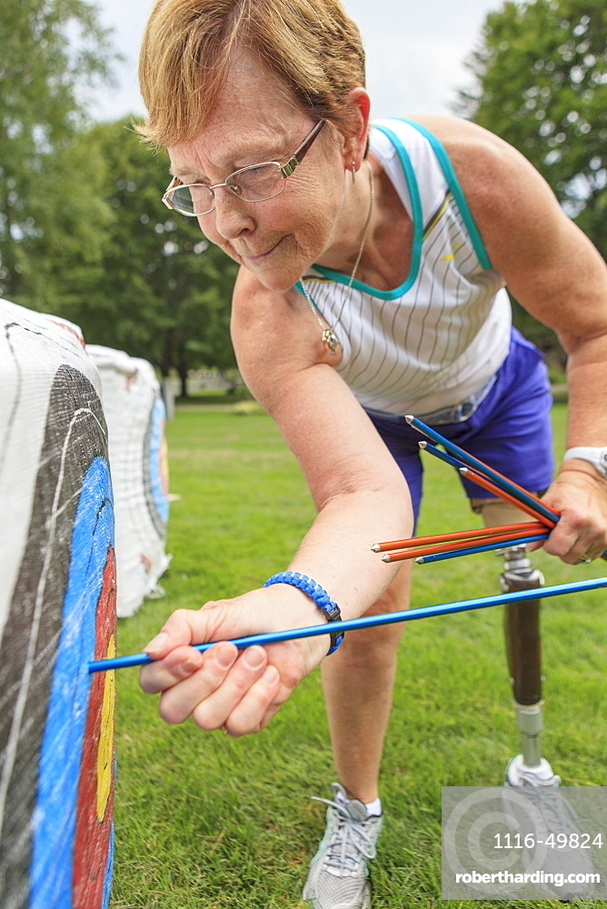 Woman with prosthetic leg pulling arrows from target after archery practice