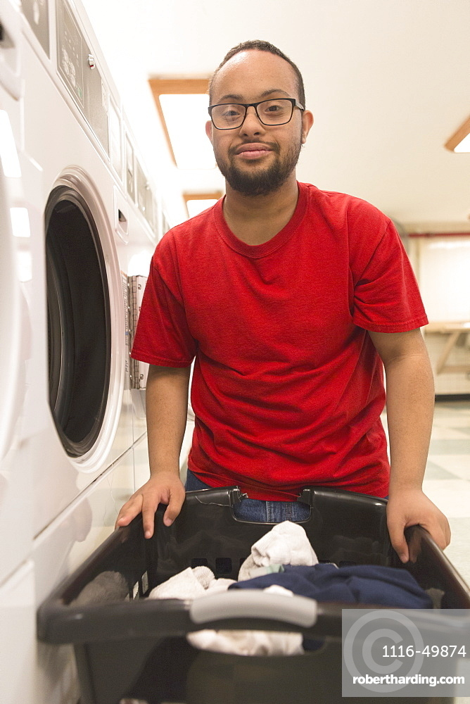African American man with Down Syndrome doing laundry in utility room