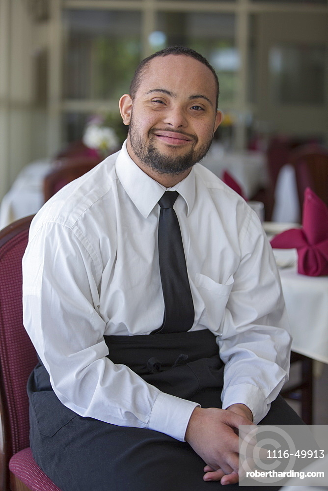 Portrait of happy African American man with Down Syndrome as a waiter in restaurant