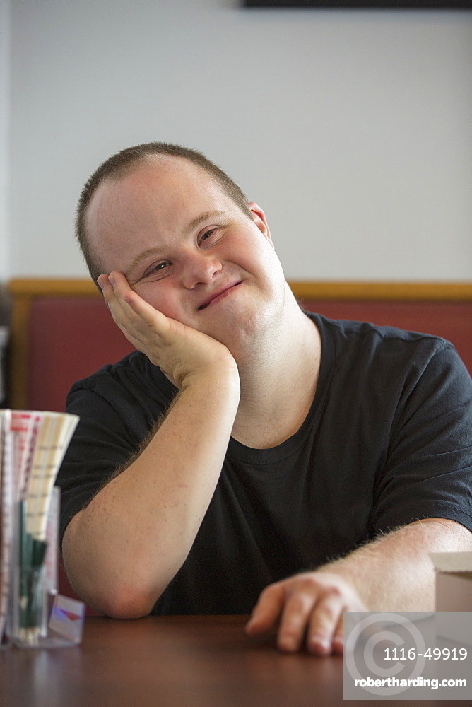 Portrait of happy waiter with Down Syndrome in a restaurant