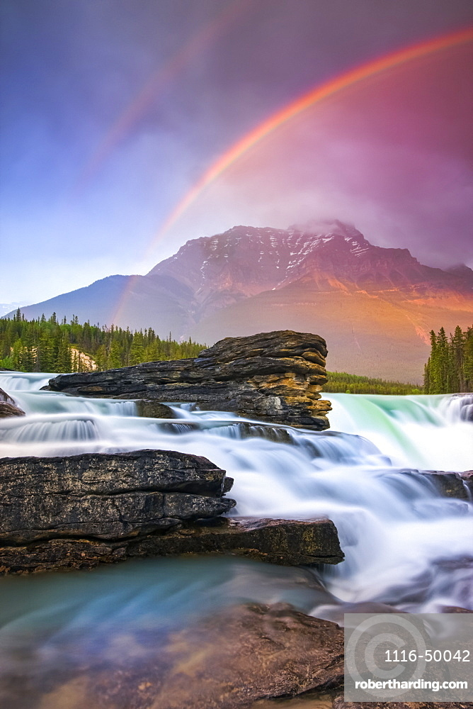 Double rainbow shining over a rugged waterfall and the Rocky Mountains, Jasper National Park; Alberta, Canada