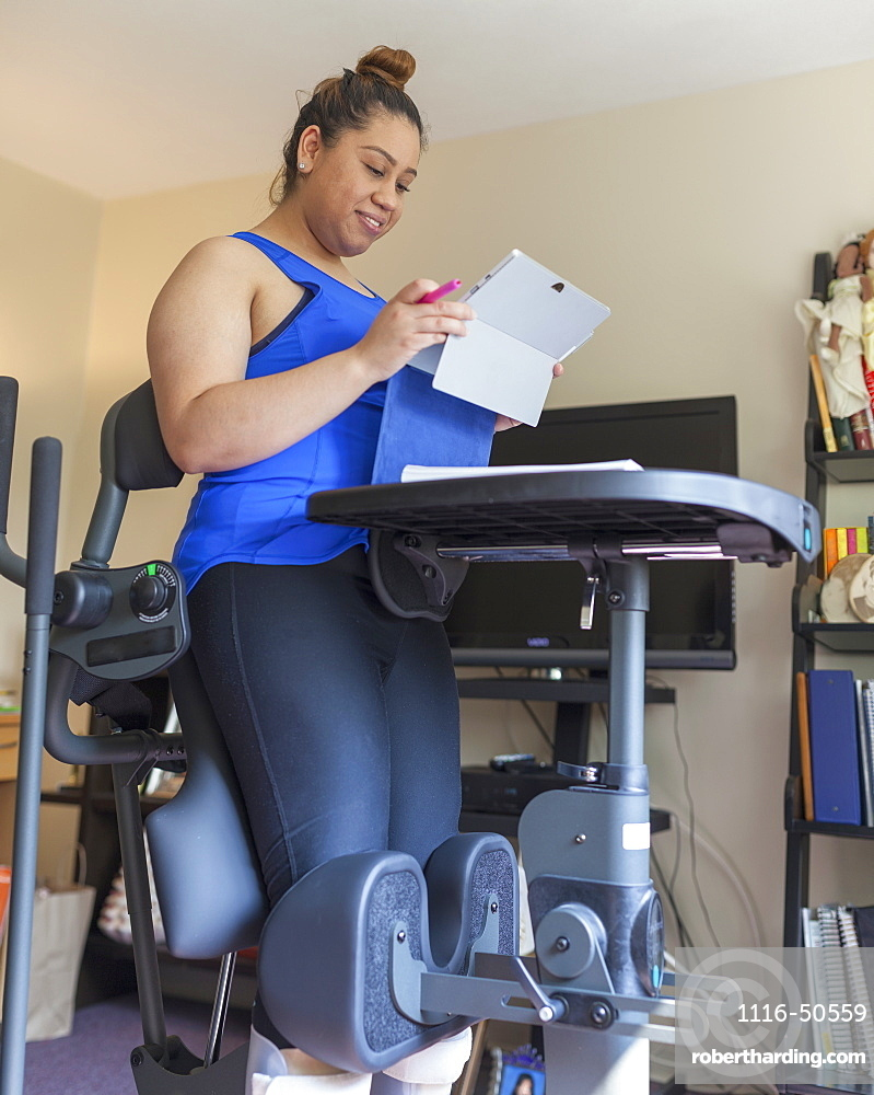 Latina woman with spinal cord injury working at home at a stand up desk