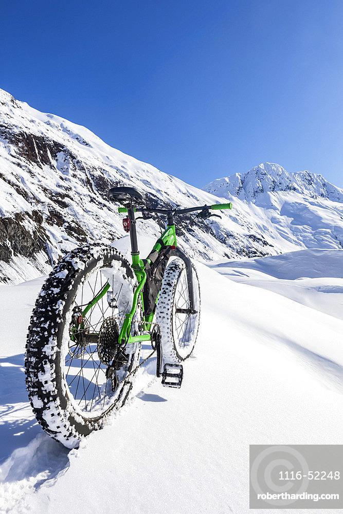Green fat tire bike on a sunny winter day at Skookum Glacier, Chugach National Forest; Alaska, United States of America