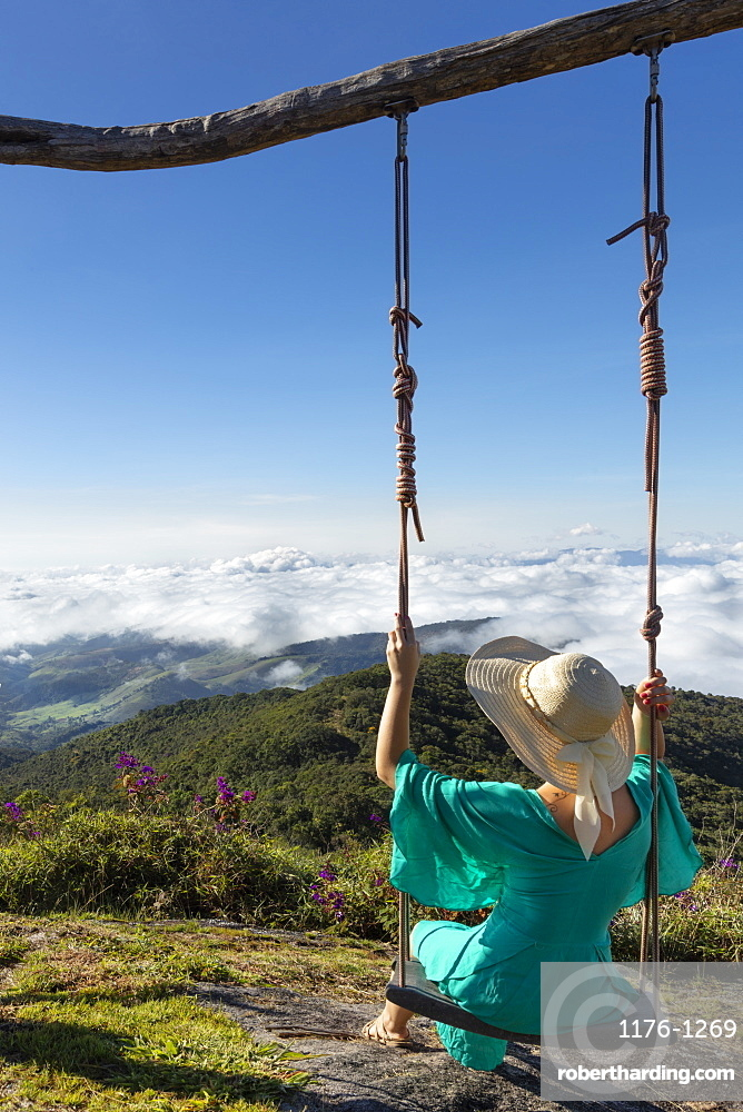 A young woman using a swing over a view of rainforest-covered mountains in the Ibitipoca Reserve