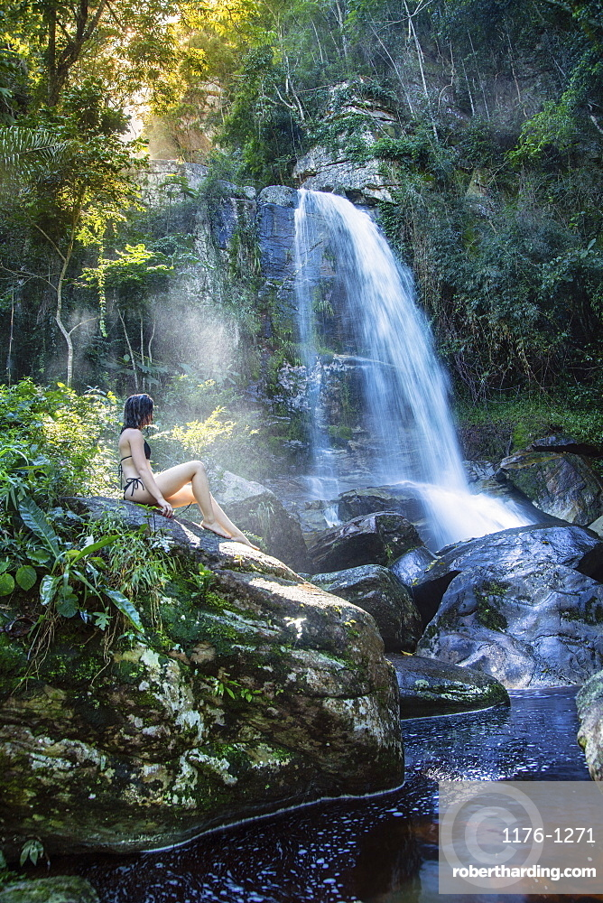 South America, Brazil. A beautiful young woman sitting in a shaft of sunlight in front of a pristine waterfall in the rainforest
