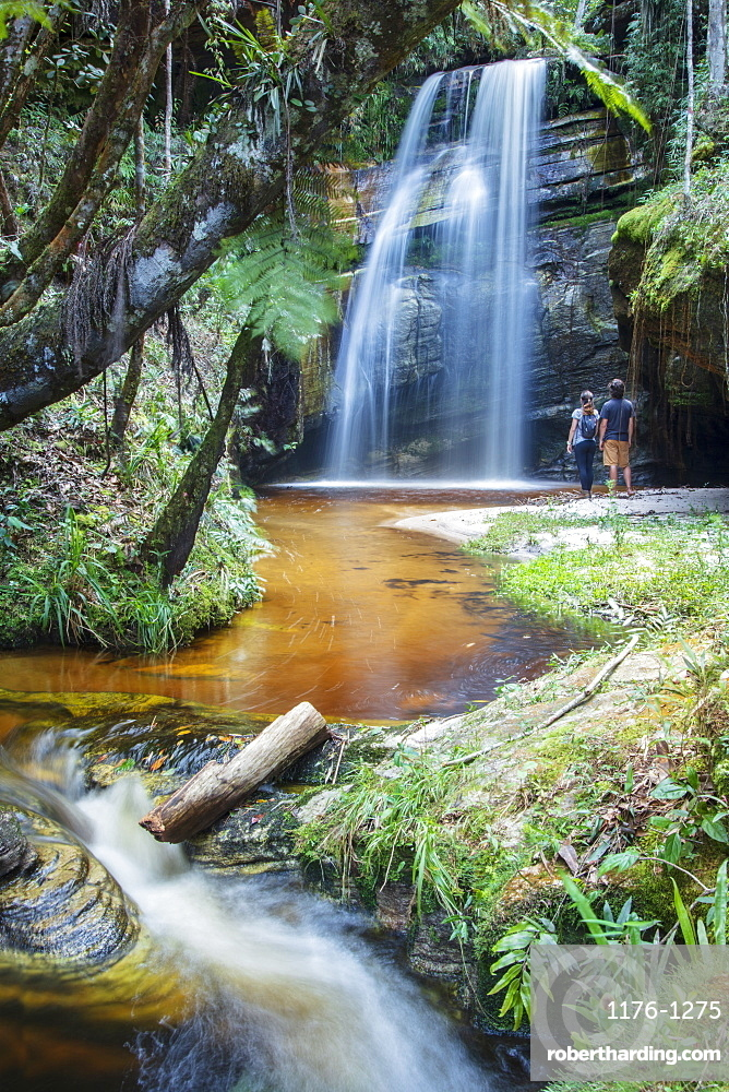 Backpackers enjoying a pristine waterfall and mountain stream in the heart of the South American rainforest