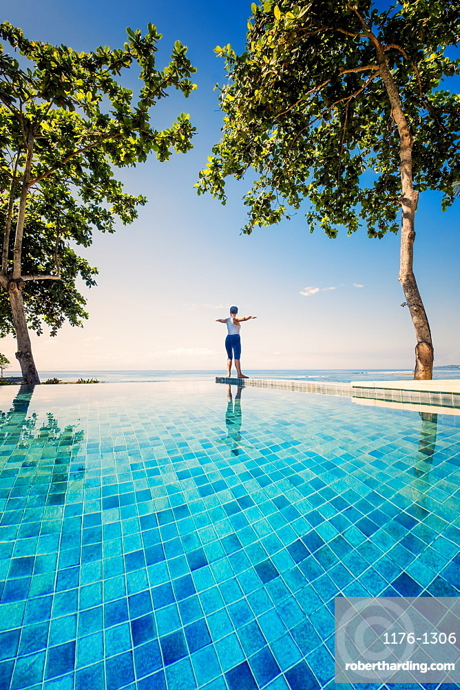 An Asian woman doing yoga exercises on the edge of an infinity swimming pool next to the sea, Indonesia, Southeast Asia, Asia