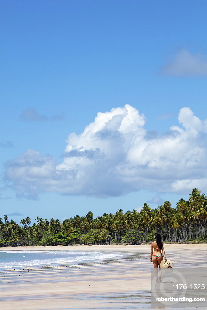 A beautiful, athletic Hispanic (Latin) woman in a bikini with a sun hat on a deserted tropical beach with back to camera, Brazil, South America