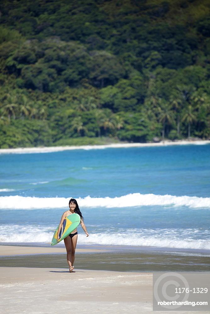 Beach shot of a Japanese Brazilian (Nipo-brasileiro) in a bikini carrying a surf board decorated with the Brazilian flag, Brazil, South America
