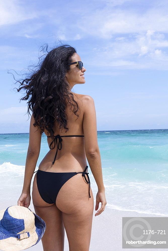 A young Brazilian woman in a bikini on Arraial do Cabo Beach, Rio de Janeiro State, Brazil, South America