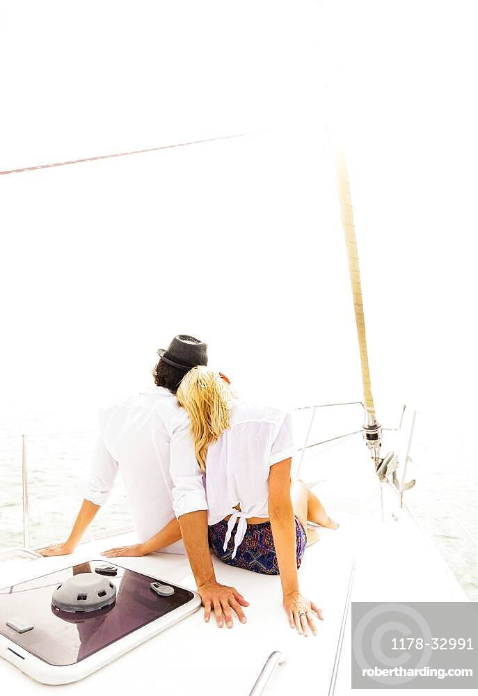 Couple cuddling on deck of sailboat