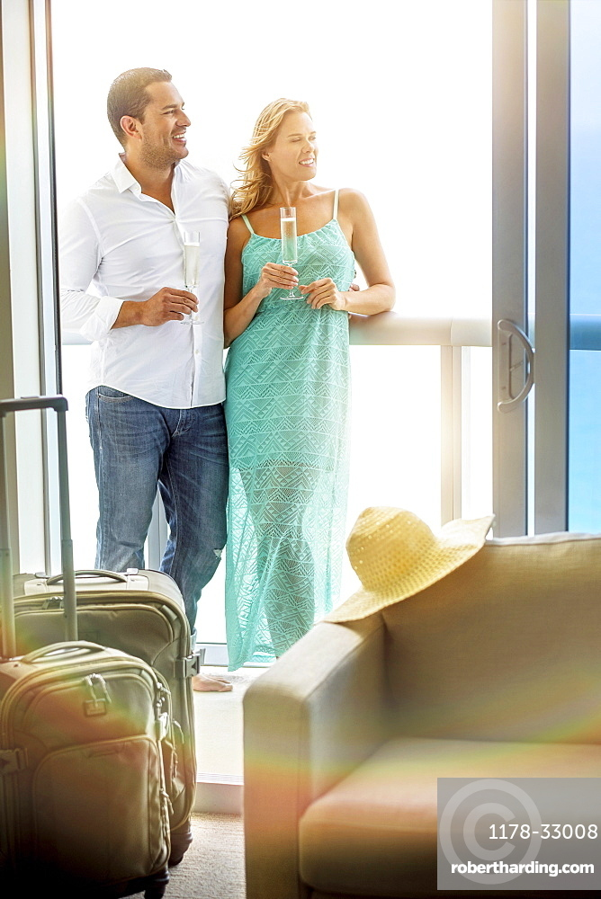 Couple drinking champagne on hotel balcony