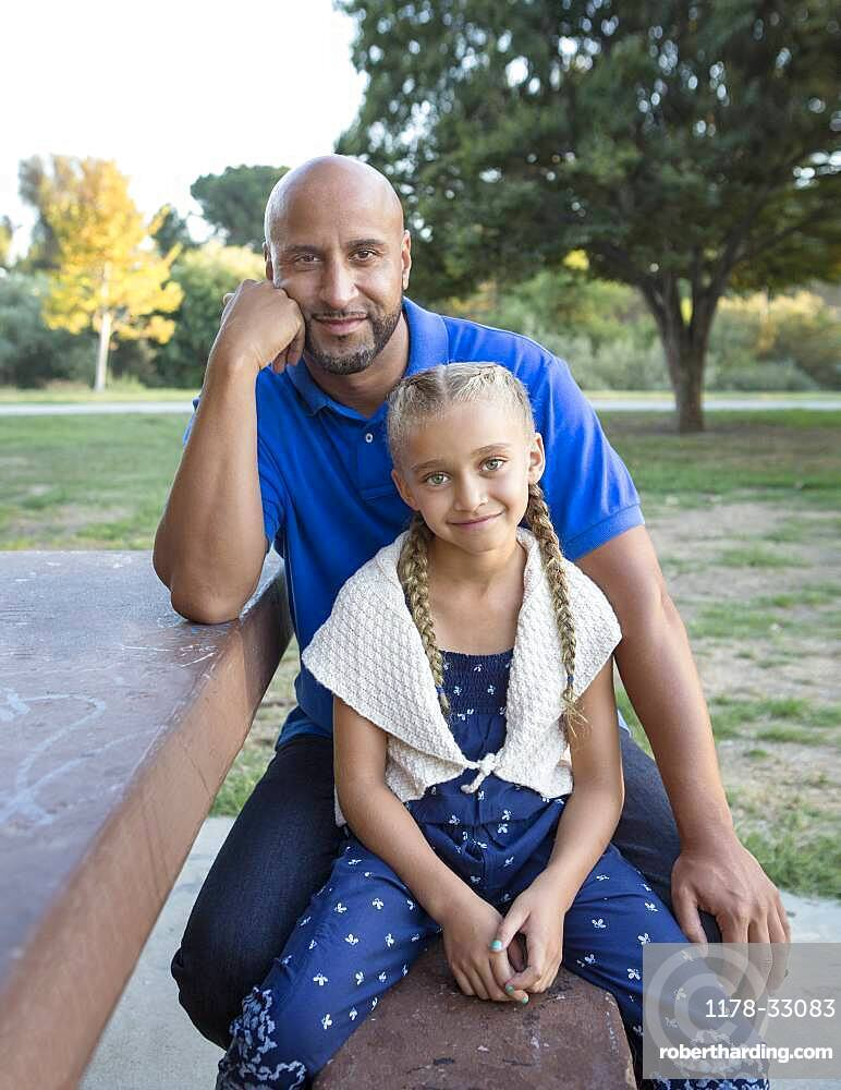 Father and daughter smiling on picnic table in park