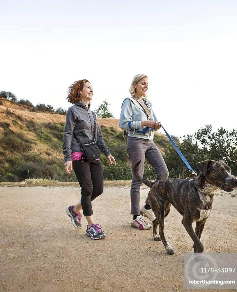Caucasian women walking dog on dirt path