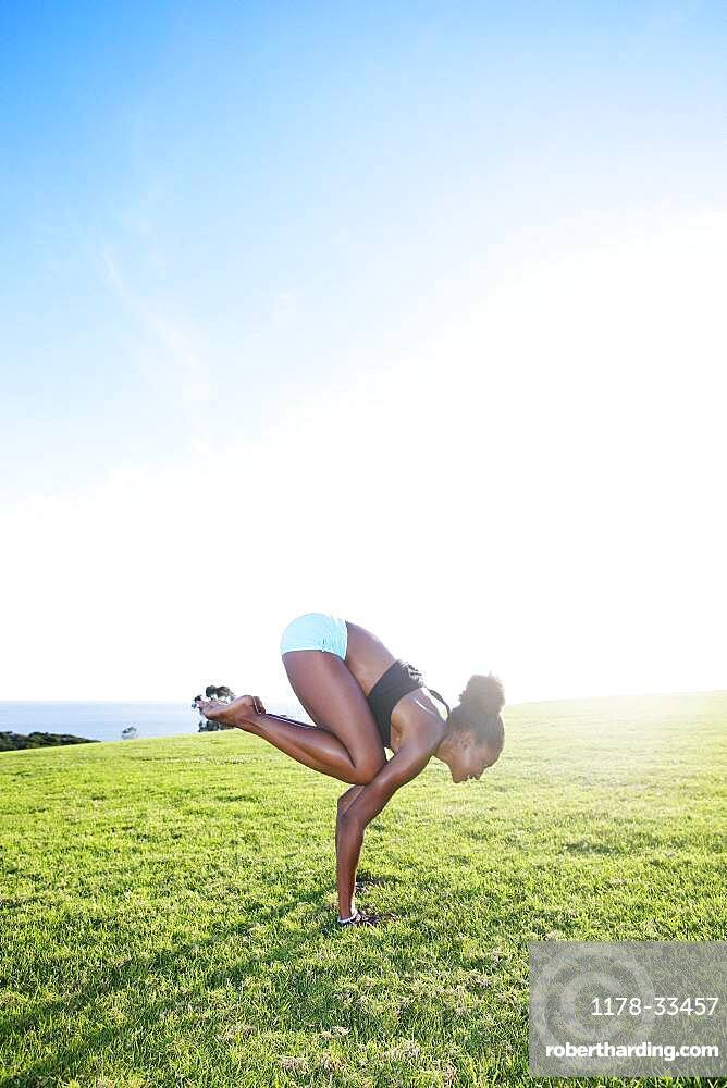 African American woman practicing yoga in park