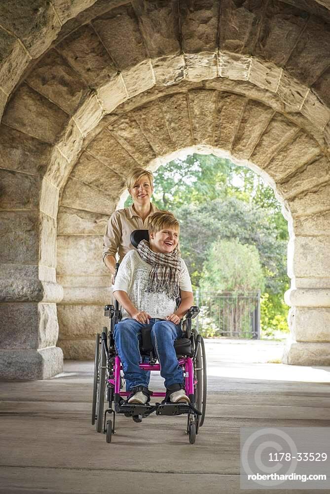 Mother pushing paraplegic daughter in wheelchair