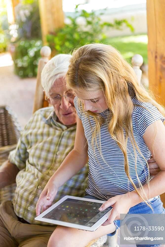 Caucasian grandfather and granddaughter using digital tablet