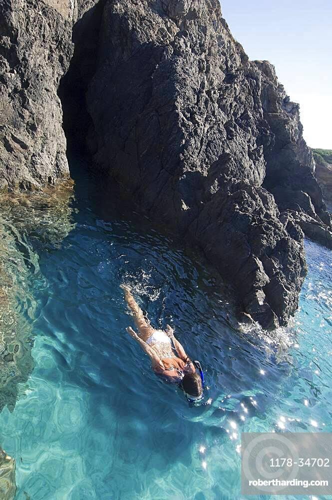 Woman swimming in ocean by rocky cliffs