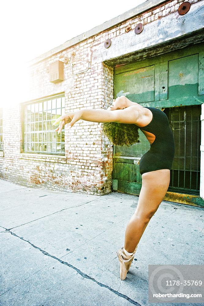 Mixed race woman dancing ballet in city