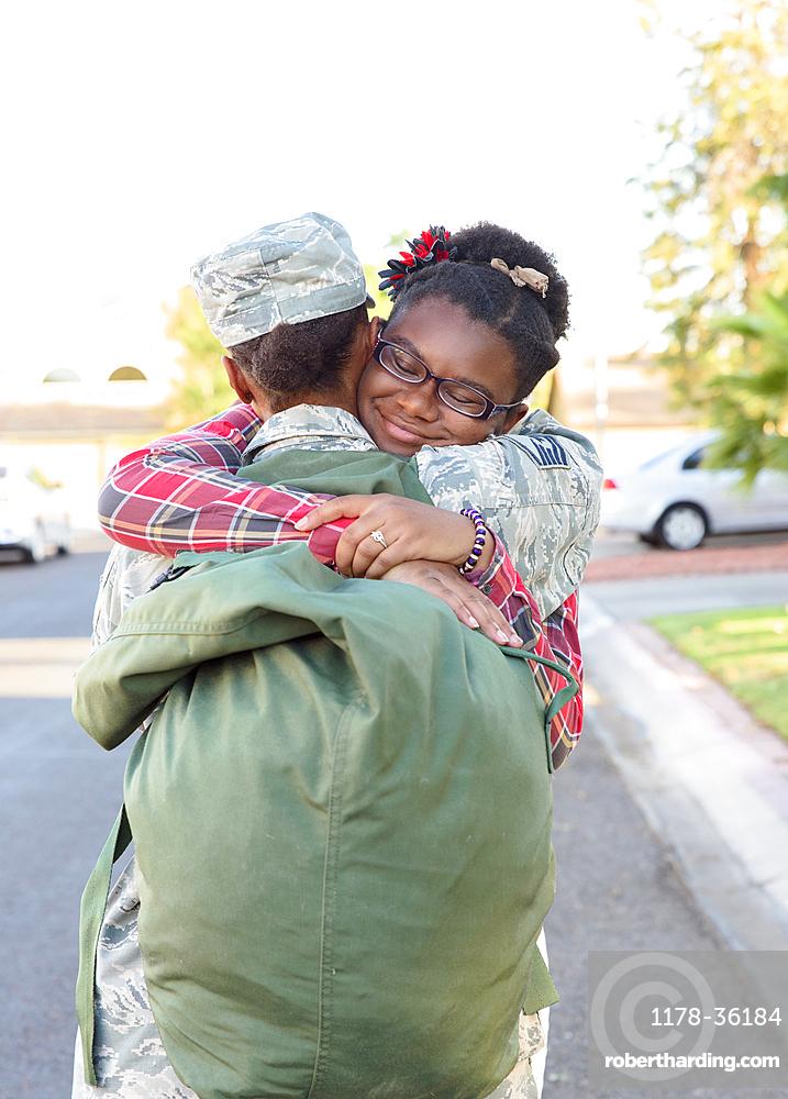 Black woman soldier hugging daughter in street