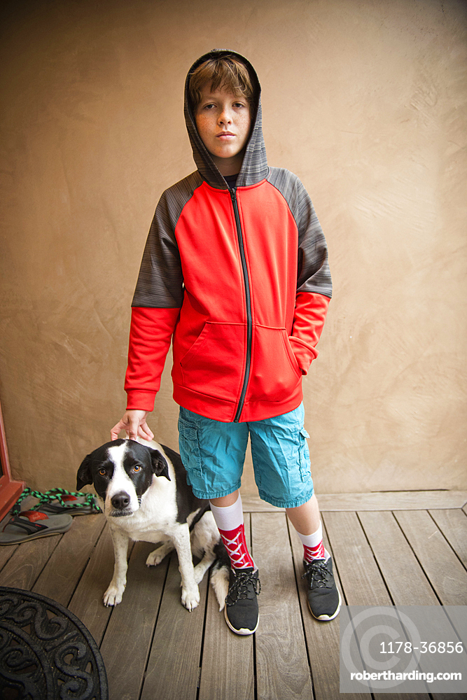 Portrait of Caucasian boy standing with dog