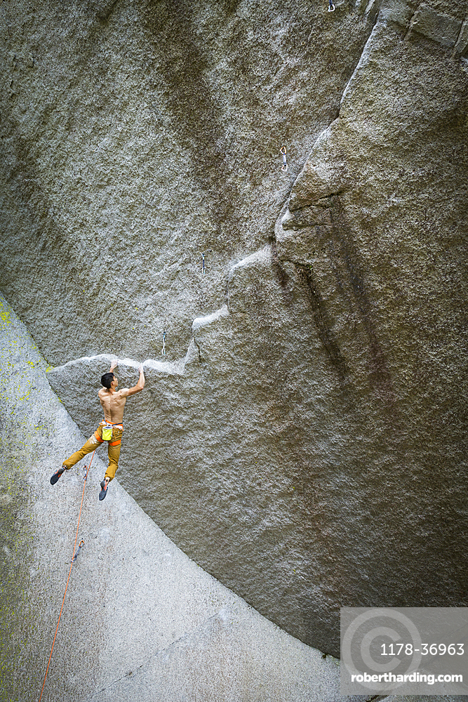 Mixed race boy hanging from rock